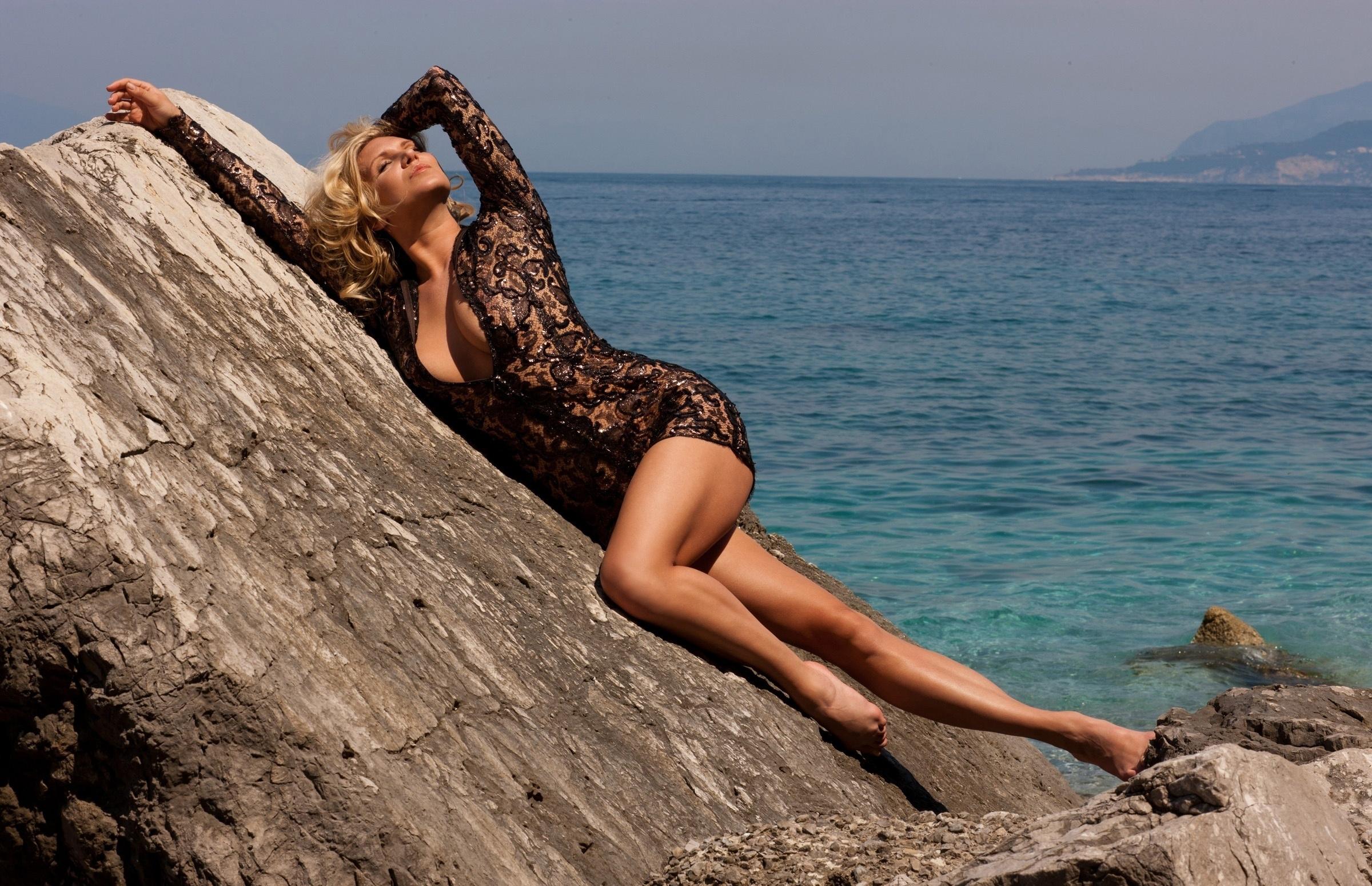 Девушка без трусов позирует на берегу моря