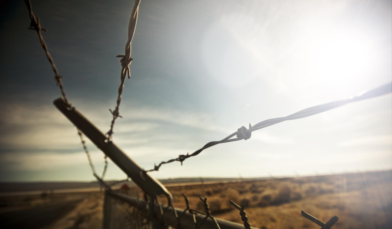 Колючая проволка на заборе  № 1701834 бесплатно