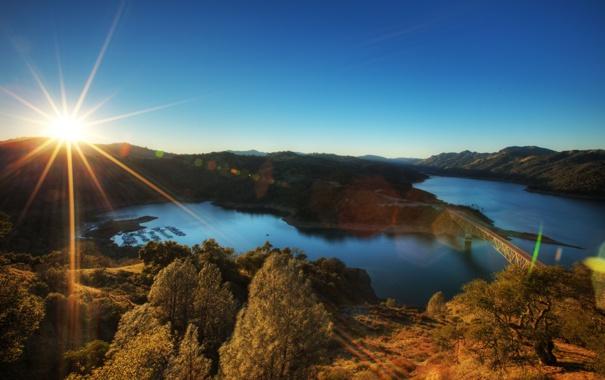 Фото обои небо, солнце, лучи, мост, река, холмы
