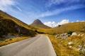 Картинка дорога, осень, небо, трава, камни, гора, склон